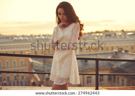 Summer outdoor porttrait of young pretty elegant girl posing at roof at sunset. Lovely soft back light. View on city buildings and roofs.