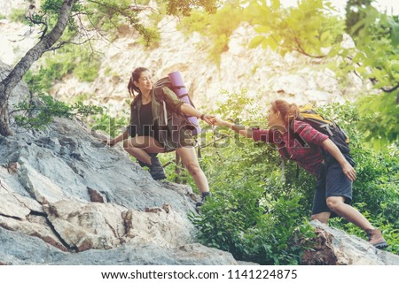 Summer Outdoors. Group Hiker woman helping her friend climb up the last section of sunset in mountains. Traveler teamwork walking in outdoor lifestyle adventure and camping. Travel Concept. #1141224875