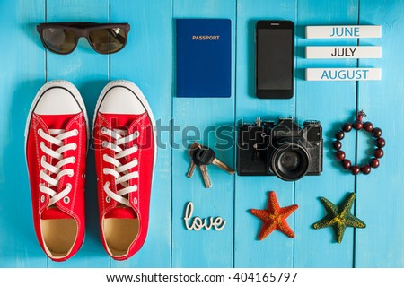 Summer outfit of traveler, student, teenager, girl, young woman or guy. Overhead Of essentials for modern Young person. Different objects on blue wooden background