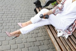 Summer outfit, street fashion look. Young tanned beautiful woman in white pants and light floral pink patent in leather high-heeled shoes. Stylish girl sitting on a bench in the city.