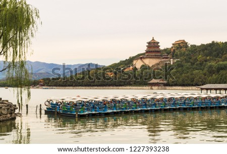 Summer Palace of emperors from dynasties of the past with the view at the lake. Tourist boats and trees in the foreground, mountain range - in the background, Beijing, China. #1227393238