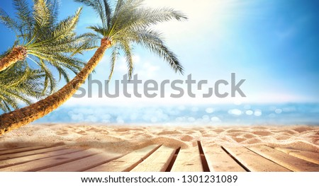 Summer  panoramic  landscape, nature of tropical beach with wooden platform, sunlight. Golden sand beach, palm trees, sea water against blue sky with white clouds. Copy space, summer vacation concept.