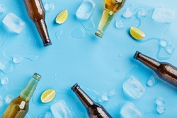 Summer party and chilled drinks. Dark and light glass beer bottles without labels with ice and pieces of lime on blue background, top view, free space