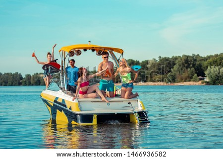 Summer party. Happy young people celebrating their friendship drinking soft drinks on the deck of a pleasure boat