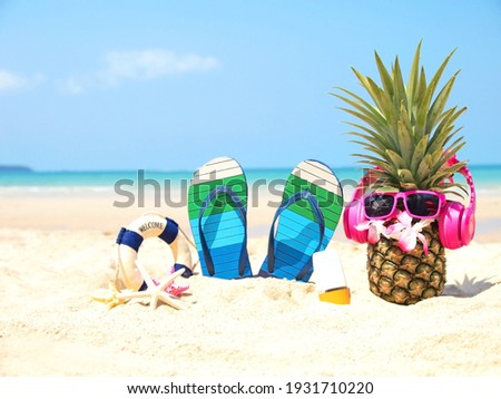 Summer party. Pineapple wearing sunglasses and listen to music with sunblock and sandal on beach and blue sky background. Tropical fashion. Summer Fashion on holiday concept.