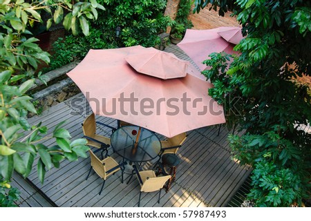Summer Patio with tables and wooden chairs under umbrella in garden