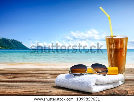 Summer photo of desk with coffee and sunglasses on towel. Free space for your decoration.