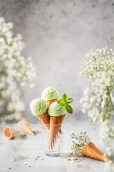 Summer photo of ice cream.  Pistachio ice cream with flowers around.  3 balls of ice cream
