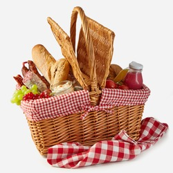 Summer picnic basket filled with food with fresh fruit and juice, spicy salami, baguettes, tomatoes and herb spread isolated on white on a rustic checked tablecloth