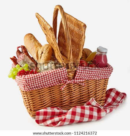 Summer picnic basket filled with food with fresh fruit and juice, spicy salami, baguettes, tomatoes and herb spread isolated on white on a rustic checked tablecloth Stockfoto ©
