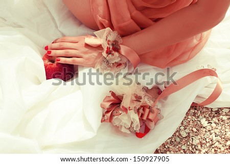 Summer picnic concept. Hand of sitting woman in trendy dress holding red apple (love symbol). Wedding accessories on white vapory cloth. Sunny weather. Outdoor shot - stock photo