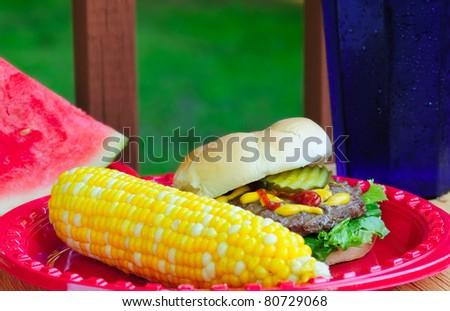 Summer picnic fare - hamburger, sweetcorn, and watermelon - in an outdoor setting