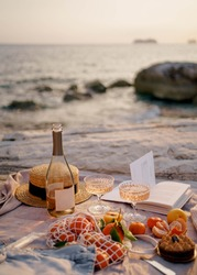Summer picnic outdoors with blanket, eco style straw hat with fruits and wine. Romantic picnic with seaside and sea view at sunset