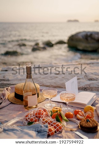 Summer picnic outdoors with blanket, eco style straw hat with fruits and wine. Romantic picnic with seaside and sea view at sunset Stock photo ©