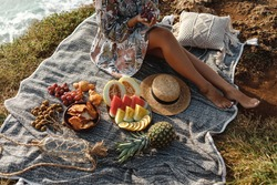 Summer picnic setting. Woman ins floral dress and straw sunhat sitting on the blanket , fresh fruit and baguette on blanket, top view. Outdoor gathering or lunch concept