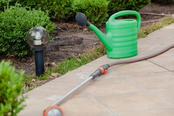 Summer plot. A green plastic watering can sits on a tile. Nearby lies a rubber hose for watering the garden