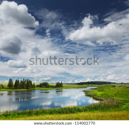 Summer pond with green meadows around and blue cloudy sky