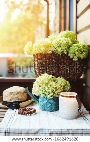 summer porch decoration with flowers and candles. Romantic evening at wooden cottage, gardening and country living concept. Foto stock ©