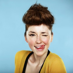 Summer portrait, beautiful freckled young woman with tongue, wearing yellow cardigan. Blue background. Studio shot