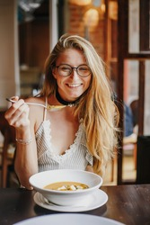summer Portrait of beautiful smiling girl sitting in cafe with plate of soup. Vegetarian. Eating lunch in a cafe.