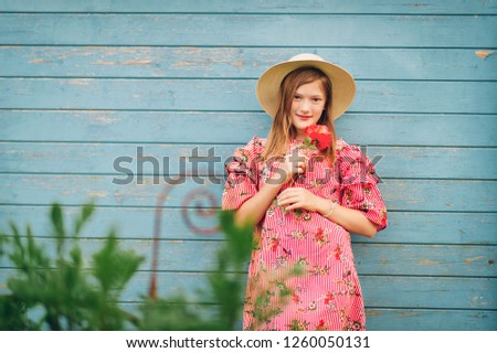 Summer portrait of cute little girl wearing red stripe dress, straw hat, holding rose flower, posing on bright blue wooden background
