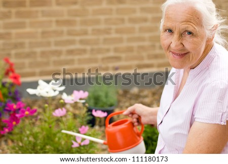 Summer portrait of elderly woman watering her flowers