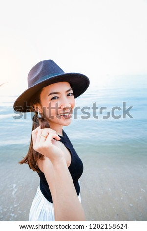 Summer portrait of glamour brown hair young woman wearing black suit, sun hat and happy smile. Standing in the sea