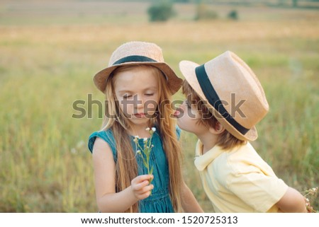 Summer portrait of happy cute children. Childhood memories. Romantic and love. Love. Love story. Childhood concept. Happy children girl and boy hug on meadow in summer in nature #1520725313