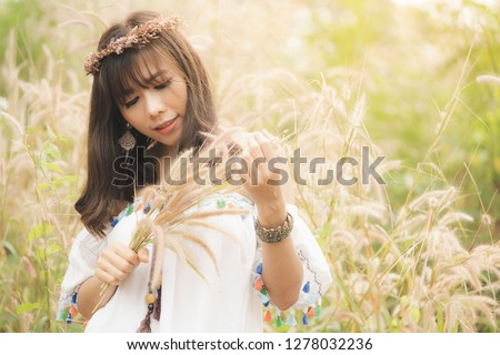 Summer portrait of young Asian hipster woman or hippie style in a grass on sunny day,Fashion vintage, Bohemian fashion, concept. trendy clothes. trendy clothes. Soft warm vintage color tone.  #1278032236