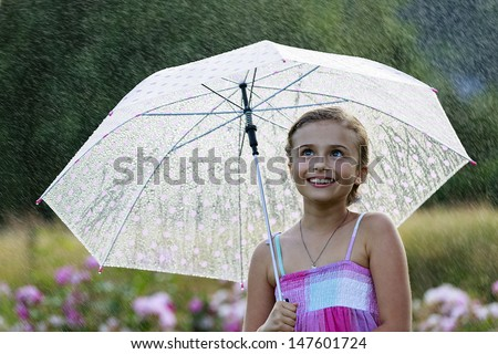 Summer rain - happy girl with an umbrella in the rain