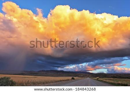 Summer rain. The huge cumulonimbus cloud is shined with the sunset sun. Rain streams shine orange light. The cloud hangs over the gravel road