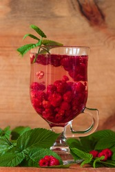 Summer raspberry cold tea in a glass on wooden background. Healthy fruit cocktail. Tasty red juice with fresh green leaves. Seasonal raspberries vitamins, colds and flu treatment hot drink. Food photo