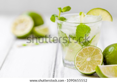 Summer refreshing cocktail mojito with lime and mint on white wooden vintage background. Fresh summertime iced drink with green citrus and fragrant leaves in beautiful glasses. #1090655552