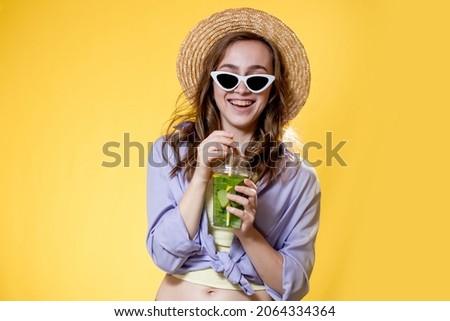 Summer refreshment. Cold beverage. Happy woman in sunglasses holding plastic glass of mojito. Non-alcoholic drink. Detox lemonade.