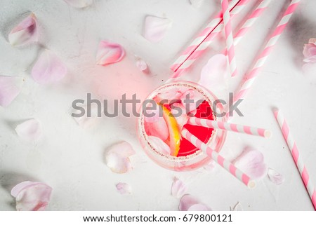 Summer refreshment drinks. Light pink rose cocktail, with rose wine, tea rose petals, lemon. On a white stone concrete table. With striped pink tubules, petals and rose flowers. Copy space top view