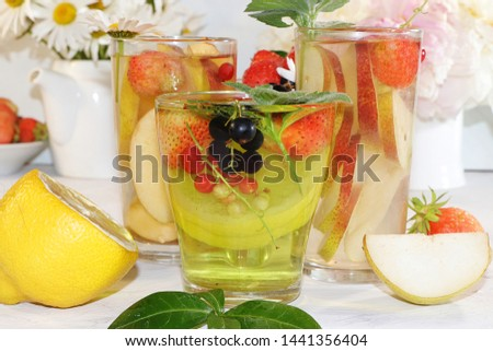 Summer refreshments and fruits, selective focus, top view, copy space ... Strawberry, pear, apple lemonade and fresh tasty strawberries and pears, chamomile flowers and mint leaves on a sunny table #1441356404