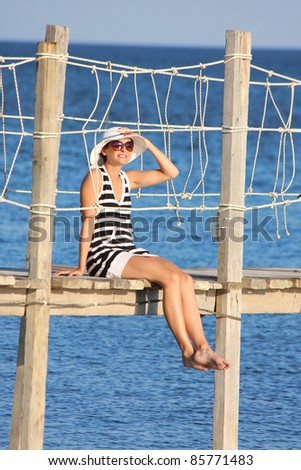 Summer relax, beautiful Woman sitting on wooden bridge over sea