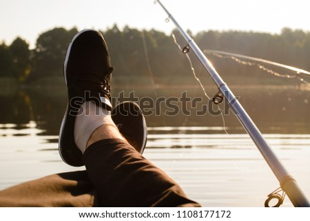 Summer relaxation on the lake while fishing. Legs of an unidentified man relaxing on the boat #1108177172
