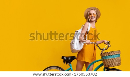 Photo of Summer Ride. Hipster Teen Girl With Hat And Backpack Riding Vintage Bike With Basket Over Yellow Background, Cropped Image, Panorama
