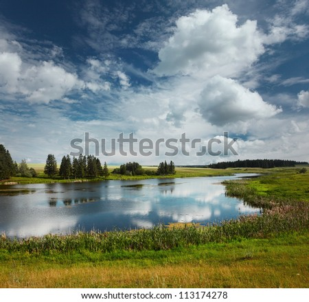 Summer river with green meadows around and blue cloudy sky