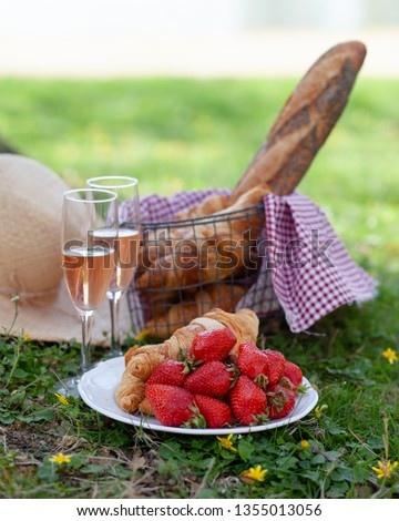 Summer romantic picnic in Paris for a couple, french style: croissants, strawberries, baguette, 2 glasses of rose wine. Authentic basket. Good sunny weather, green grass, vacations, romance, lifestyle #1355013056