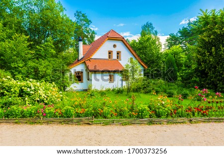 Photo of  Summer rural cottage view. Cottage house scene. Cottage garden in summer. Summer cottage garden