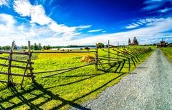 Summer rural farm road fence. Village road fence. Summer rural road fence. Farm fence road