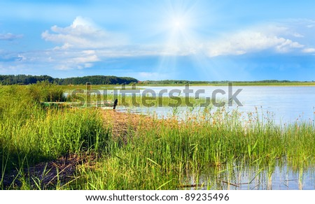 Summer rushy lake view with wooden boat near shore