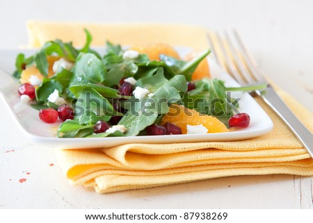 Summer salad of baby spinach, pomegranate and oranges topped with crumbled feta cheese. - stock photo