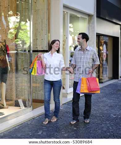 summer sale: couple with shopping bags in front of a store
