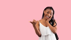 Summer sale. Emotional black lady pointing at blank space over pink studio background, banner design. Pretty African American woman in trendy clothes having special offer, advertising your product