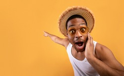 Summer sale. Shocked black guy in straw hat pointing at empty space on yelow studio background. Surprised African American man advertising your summertime product or service