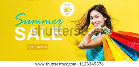 Summer sale with happy young woman holding shopping bags on a yellow background