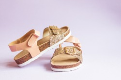 Summer sandals for children with shades of pink and gold glitter over purple background isolated.